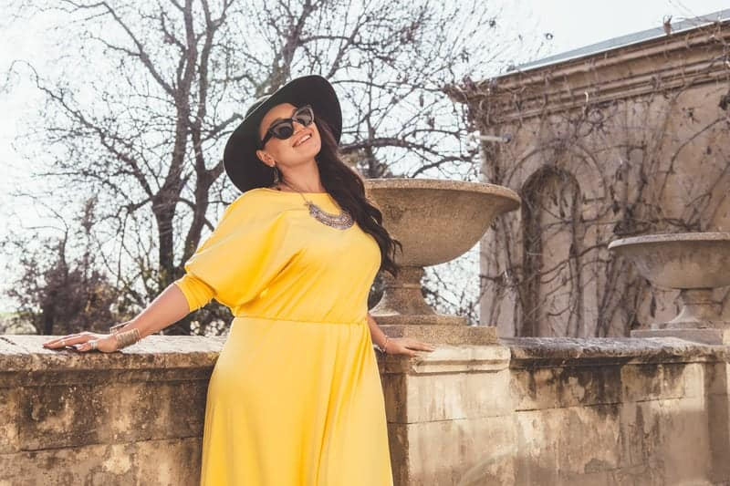 woman in yellow dress, hat, and shades
